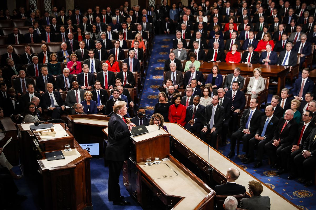 President Trump is standing behind the podium of the House of Representatives delivering his State of the Union Address, looking into a crowd of seated legislators in the auditorium.