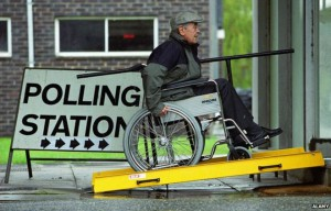 "Elderly caucasian man with a jacket and baseball hat on, using a manual wheelchair, is pushing himself up a bright yellow portable ramp, next to a big sign, which reads, ""POLLING STATION,"" with arrows pointing the direction he is going."