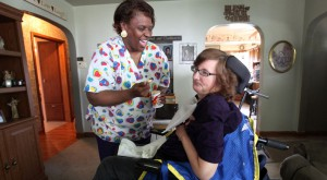 An African American Personal Care Attendant smiles as she feeds yogurt to a woman using a power wheelchair