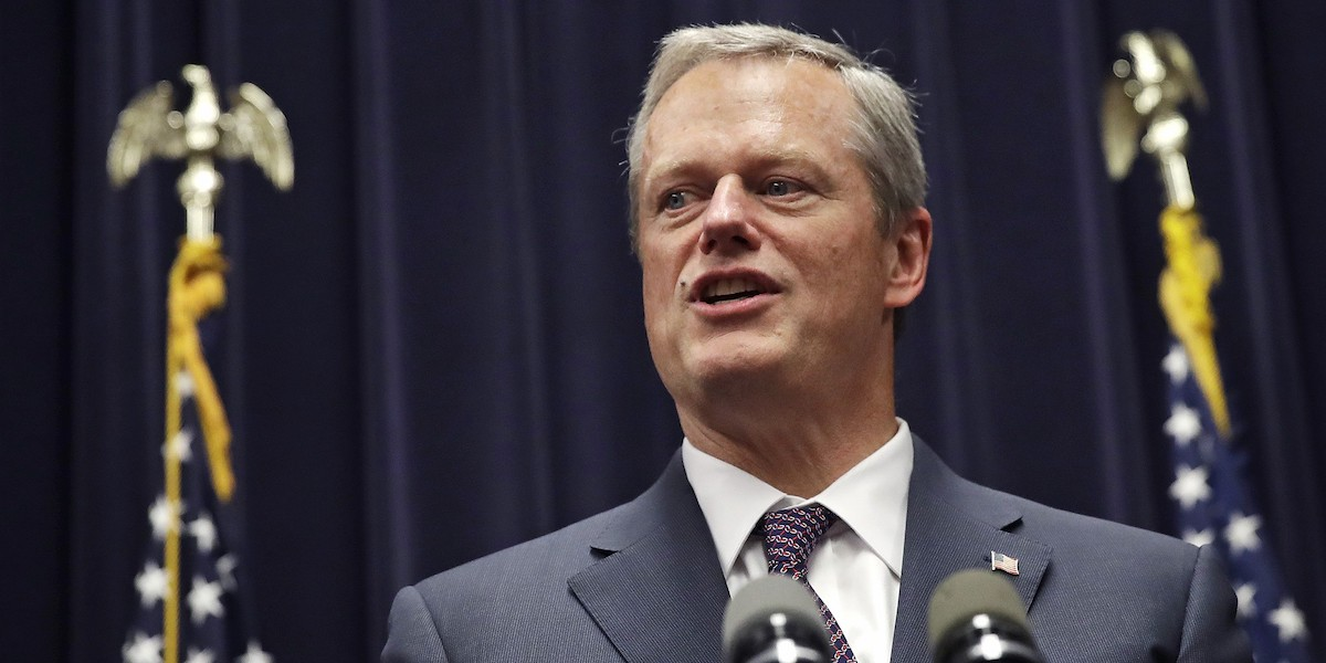 Governor Charlie Baker speaking in front of a blue curtain and two American flags
