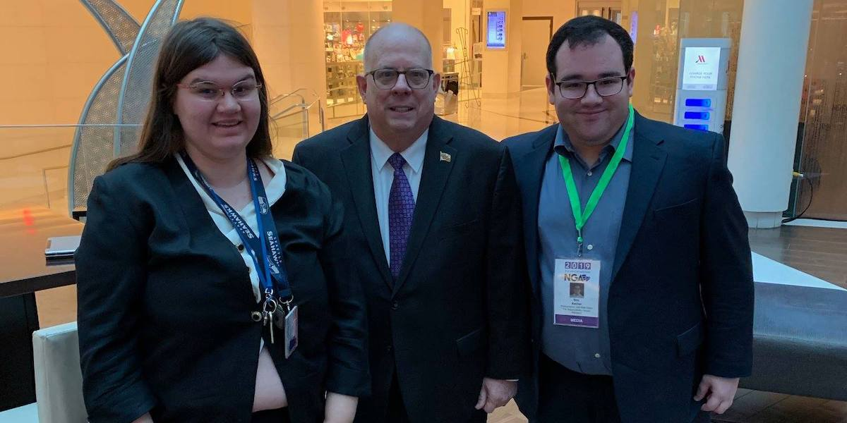 L-R: Heidi Wangelin, Maryland Governor Larry Hogan, and Eric Ascher smile together in the Marriot Marquis Lobby.