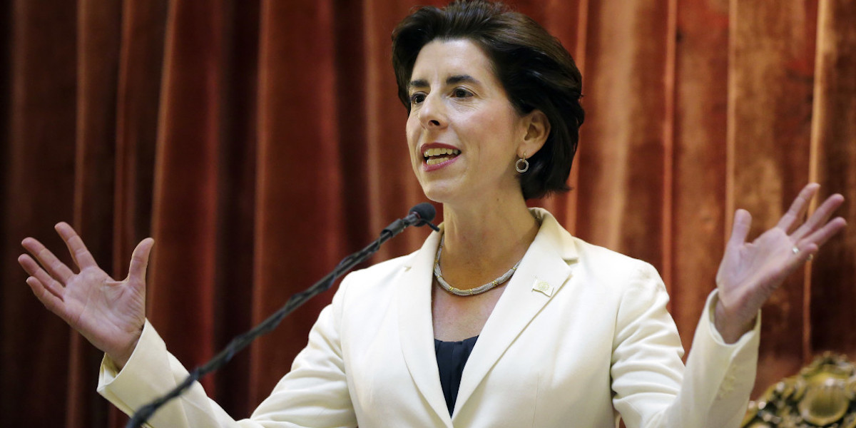 Rhode Island Governor Gina Raimondo speaking in front of a curtain, smiling, with her hands up by her shoulders
