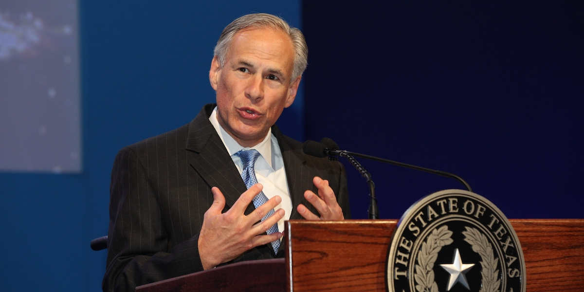 Governor Greg Abbott speaking behind a podium with the seal of the state of Texas on it
