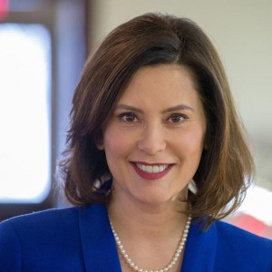 Michigan Governor Gretchen Whitmer smiling in front of a blurred background