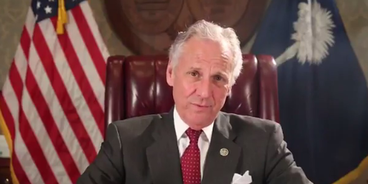 Governor Henry McMaster sitting at his desk in front of an American Flag and a South Carolina state flag giving a speech