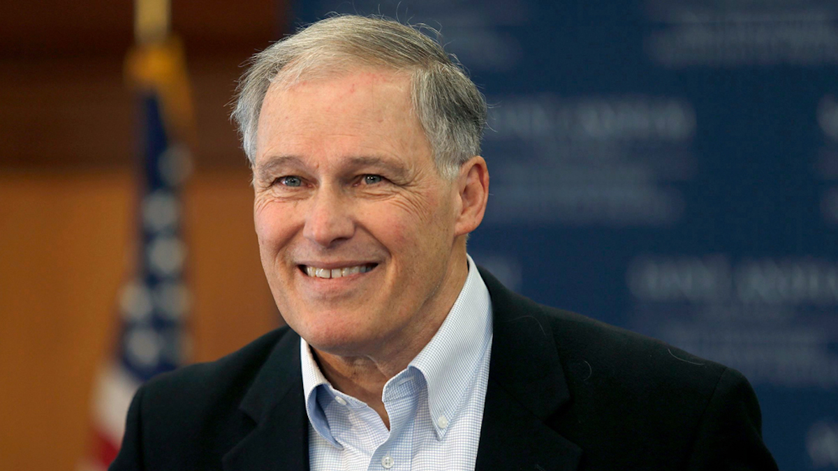 Jay Inslee in front of a blurred background of an American flag and a blue wall
