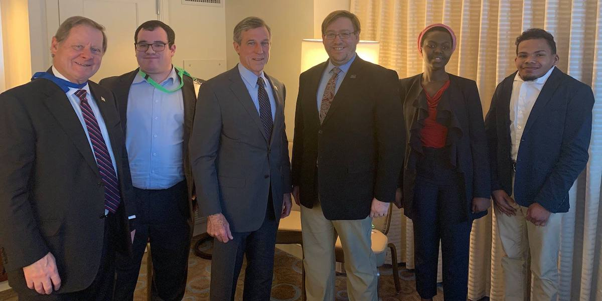 Delaware Governor John Carney with RespectAbility staff and Fellows, smiling