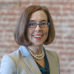 Oregon Governor Kate Brown smiling in front of a blurred brick wall