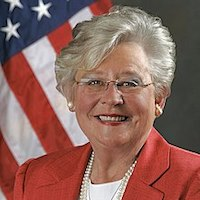 Governor Kay Ivey smiles in front of an American flag