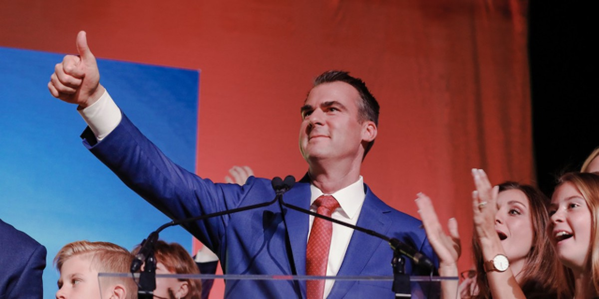 Governor Kevin Stitt giving a thumbs up on stage with supporters behind him