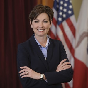 Iowa Governor Kim Reynolds smiles in front of the American flag and the Iowa State flag