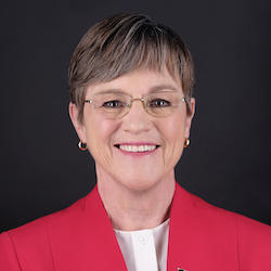 Kansas Governor Laura Kelly smiling in front of a black backdrop
