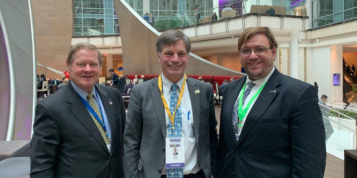 L-R: Steve Bartlett, Wyoming Governor Mark Gordon, and Philip Kahn-Pauli smile in the Marriot Marquis Lobby