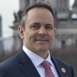 Kentucky Governor Matt Bevin wearing a suit smiles in front of a blurred background of an old building