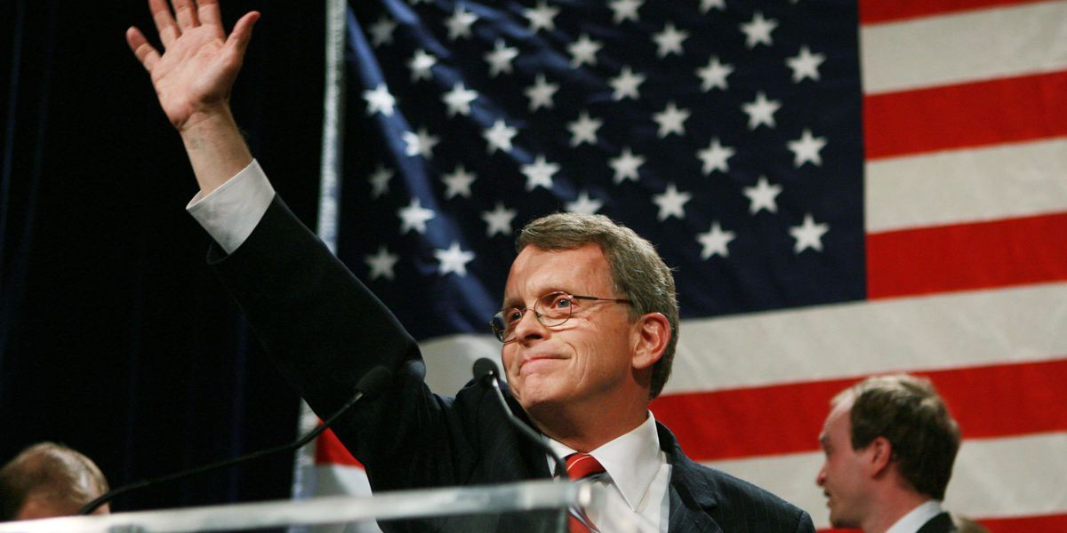Governor Mike DeWine with his right hand raised in the air in front of an American flag on stage