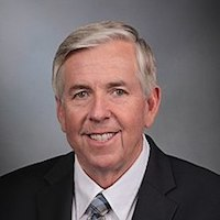 Missouri Governor Mike Parson smiling in front of a grey backdrop