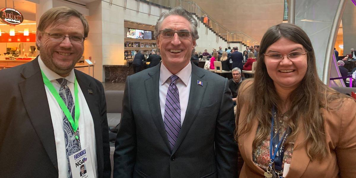 Philip Kahn-Pauli, North Dakota Governor Doug Burgum, and Heidi Wangelin smile together in the Marriot Marquis lobby