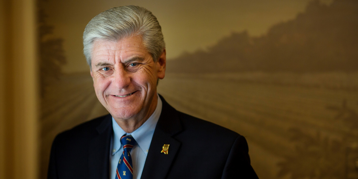 Governor Phil Bryant smiling in front of a painting of mountains