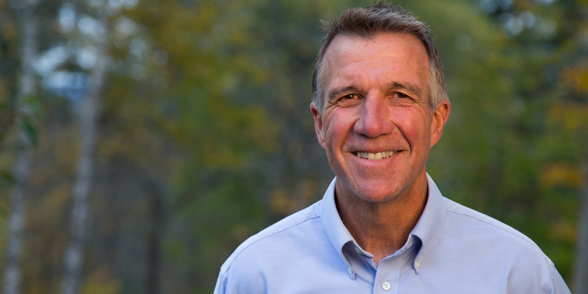 Governor Phil Scott smiles in front of blurred trees in the background