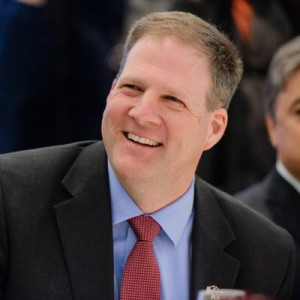 Governor Christopher Sununu smiling looking to the right of the camera