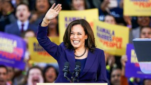 Kamala Harris waves and smiles to a crowd holding up supportive campaign posters