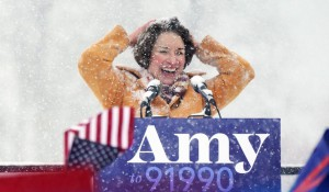 Amy Klobuchar laughs behind a podium at her announcement speech, covered in snow, amidst a blizzard