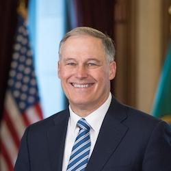 Washington Governor Jay Inslee smiling in front of an American flag wearing a suit and tie