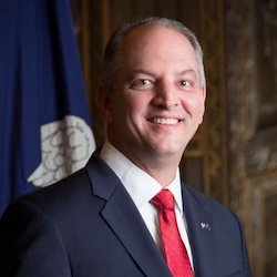 Louisiana Governor John Bel Edwards smiling in front of the state flag