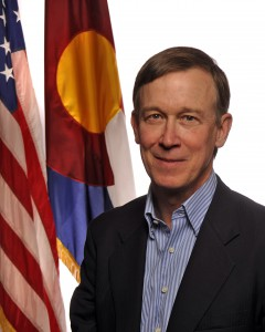 John Hickenlooper smiles next to the flags of the U.S.A. and the State of Colorado