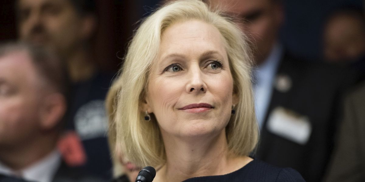Kirsten Gillibrand smiling in front of a blurred crowd background