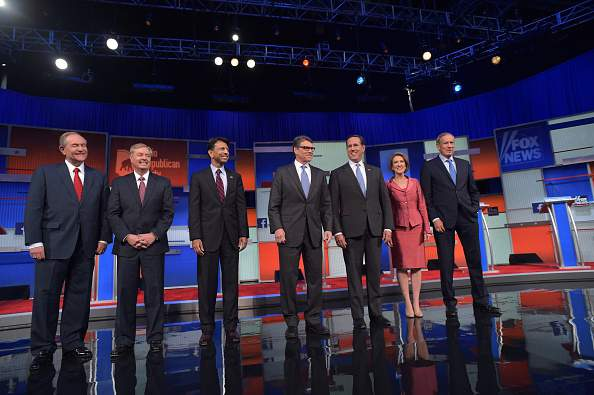Republican presidential hopefuls (L-R) Jim Gilmore, Lindsey Graham, Bobby Jindal, Rick Perry, Rick Santorum, Carly Fiorina and George Pataki arrive on stage for the start of the Republican presidential primary debate on August 6, 2015 at the Quicken Loans Arena in Cleveland, Ohio. The seven candidates will debate before the top 10 candidates face off during prime time. AFP PHOTO/MANDEL NGAN