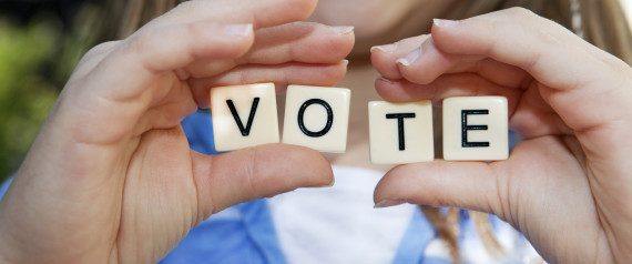 Young girl holding small block letters: Vote