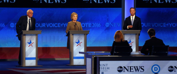 Bernie Sanders, left, Hillary Clinton, center, and Martin O'Malley take the stage for a Democratic presidential primary debate Saturday, Dec. 19, 2015, at Saint Anselm College in Manchester, N.H. Seated at the table are debate moderators Martha Raddatz, left, and David Muir, of ABC News. (AP Photo/Jim Cole)