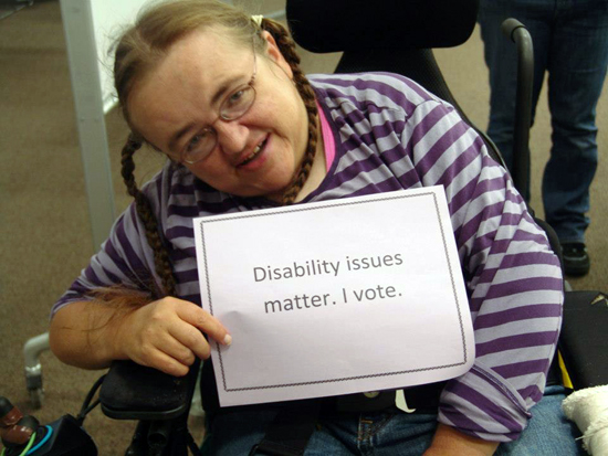 "A voter holding a sign saying ""Disability issues matter. I vote."""