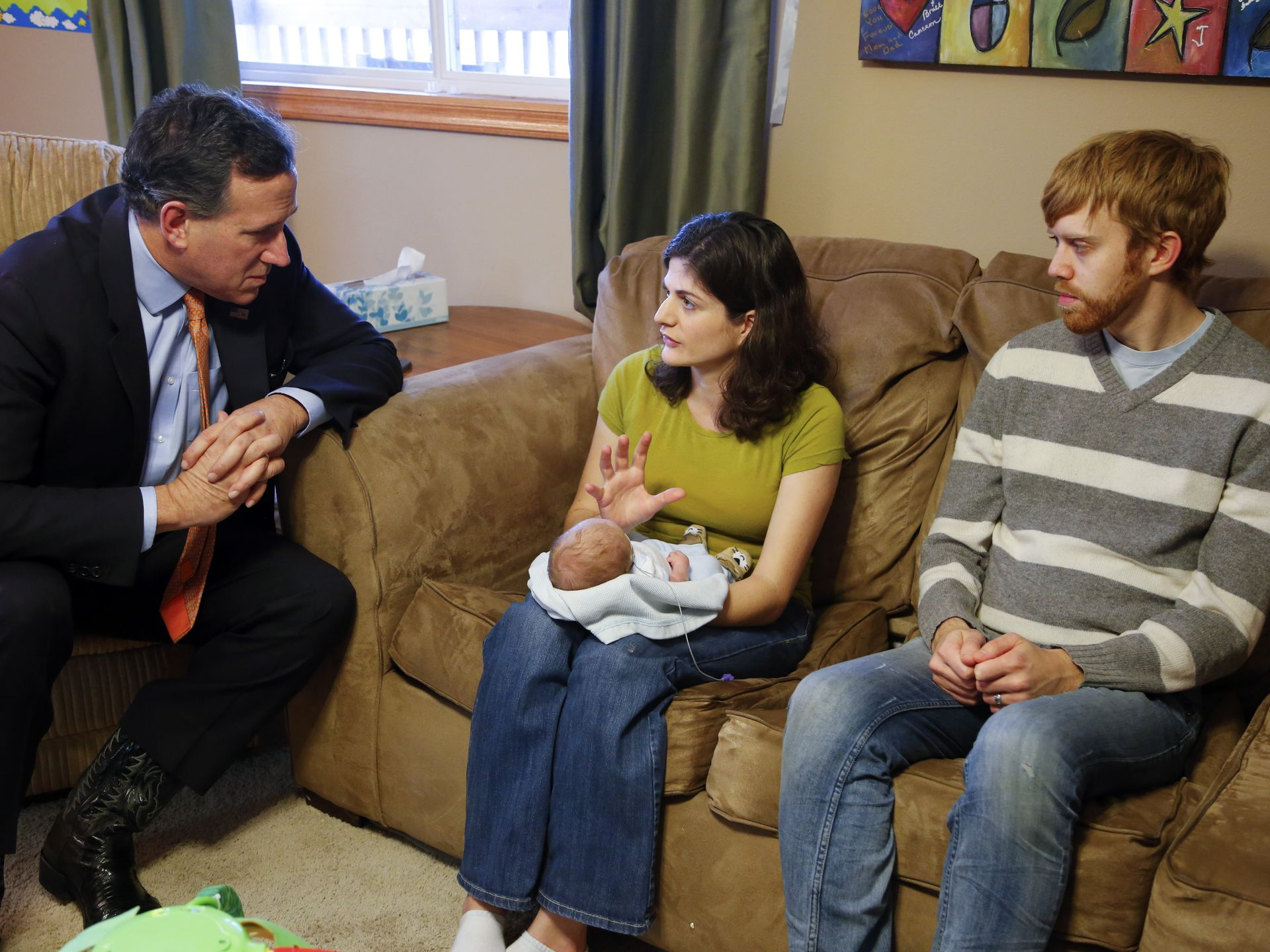 Republican presidential candidate Rick Santorum speaks with Katie and Ryan Buck at their home in rural Cumming, Iowa Thursday, Jan. 7, 2016. Their newborn baby Alex Buck, has Trisomy 18, a genetic disorder that Santorum's daughter Bella also has. Zach Boyden-Holmes/The Register
