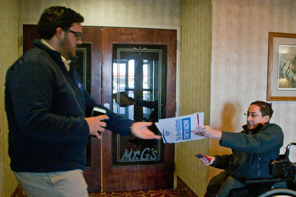 Image of RespectAbility's Justin Chappell handing signs to Ryan Nobile
