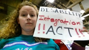 "Stephanie Woodward holding a sign saying ""Disability Integration Act"" at a Ted Cruz rally in Rochester, New York"
