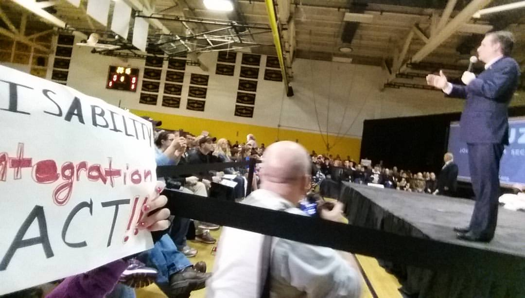 """Partial view of sign saying """"Disability Integration Act"""" being held by a woman to the side of stage with Sen. Ted Cruz standing and speaking"""