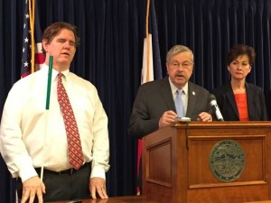 Image of Jeff James in a white shirt and red tie holding a white cane standing next to Gov. Terry Branstad and Lt. Gov Kim Reynolds who are standing behind a podium.