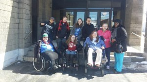 Image of eight people outside  - five standing and three in wheelchairs