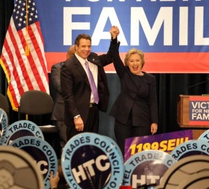 Hillary Clinton and Gov. Cuomo holding hands on a stage with people holding signs saying HTC in front of them