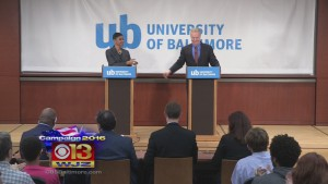 Reps. Donna Edwards and Chris Van Hollen standing behind podiums with a sign behind saying University of Baltimore