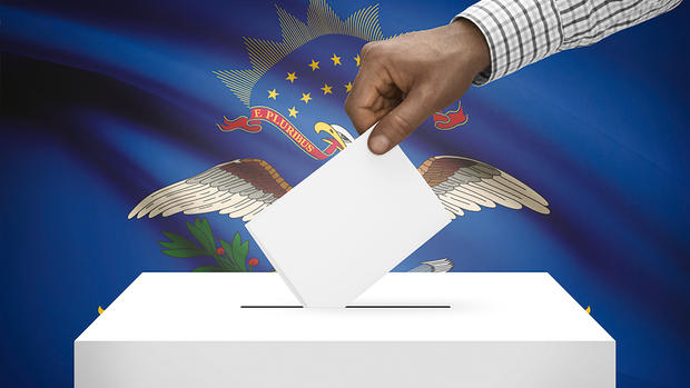 Image of man putting a card into a ballot box in front of North Dakota's flag