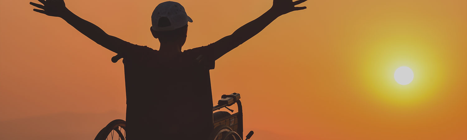 Young man in a wheelchair with arms stretched out against backdrop of rising sun