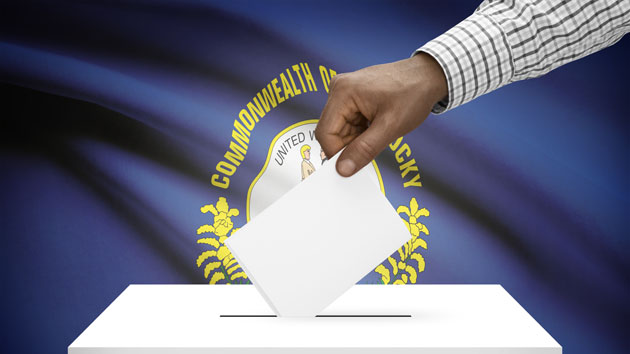 Image of man putting a card into a ballot box in front of Kentucky's flag