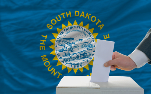 Image of man putting a card into a ballot box in front of South Dakota's flag