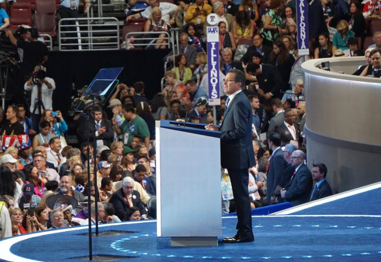 Shot from the side showing crowd behind Gov. Malloy speaking at DNC, standing behind podium, wearing black suit, white shirt and blue tie
