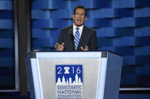 Gov. Malloy speaking at DNC, standing behind podium, wearing black suit, white shirt and blue tie