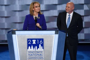 Image of Gabby Giffords speaking behind podium with husband Mark  Kelly standing next to her