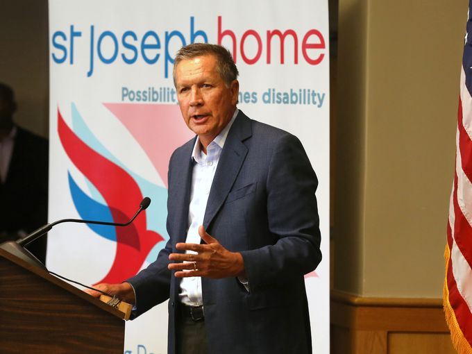John Kasich standing in collared shirt and blazer behind a podium